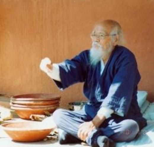 Masanobu Fukuoka throwing the first seedball at the workshop at Navdanya in October, 2002