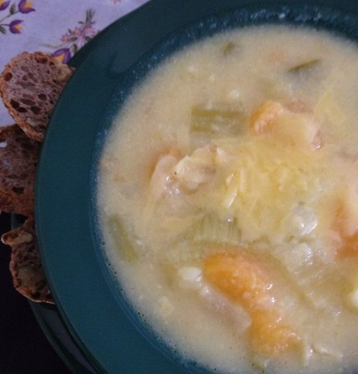 Bowl of Cheesy Potato Rutabaga Soup with crusty walnut levain