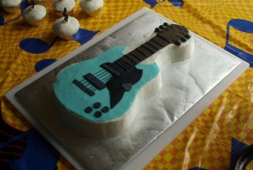 Scott's cake was made with the Wilton guitar shaped pan. An electric guitar template was used to cut out the design in fondant. Isn't it awesome?