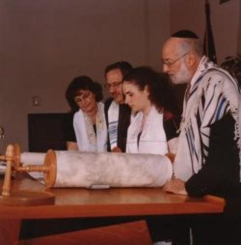 A Bat Mitzvah reading from the Torah for the first time, flanked by her rabbi and her parents.