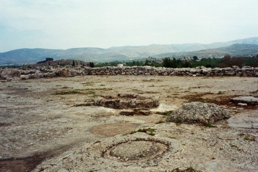 The Megaron of the Palace of Tiryns. It's hard to visualize, but this would've been a great hall with a hearth in the middle (the stone ring) supported by four large wooden columns on stone bases (one visible in foreground).