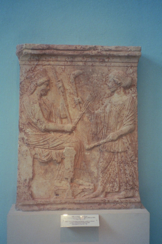 "5th century BCE. Demeter seated, Persephone holding a torch. The ""illumination"" symbolism of torches is connected to purification, death and rebirth."