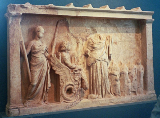 Relief from Eleusis. Apparently it's Persephone (or Hekate?), Triptolemos on a winged chariot (note serpents), Demeter, and ordinary mortals. I'm guessing this is Triptolemos bringing the sacred knowledge of grain cultivation to humankind after his i