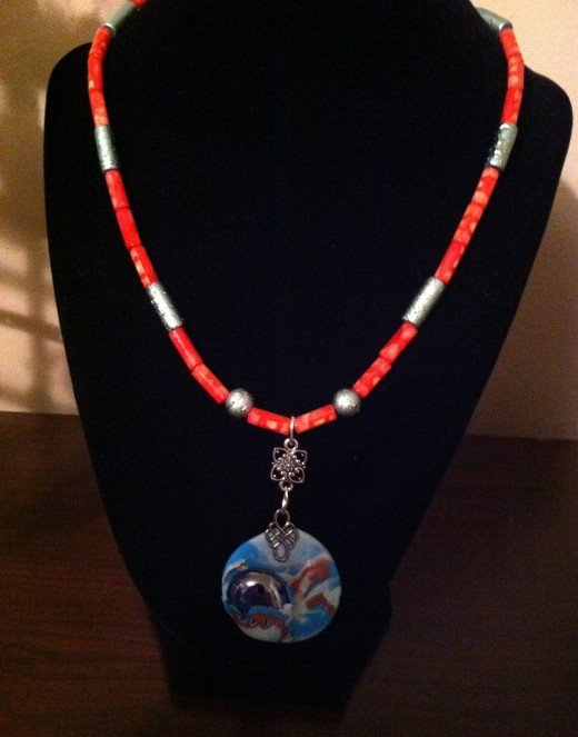 Coral and teal beads highlight the colors in the focal bead.
