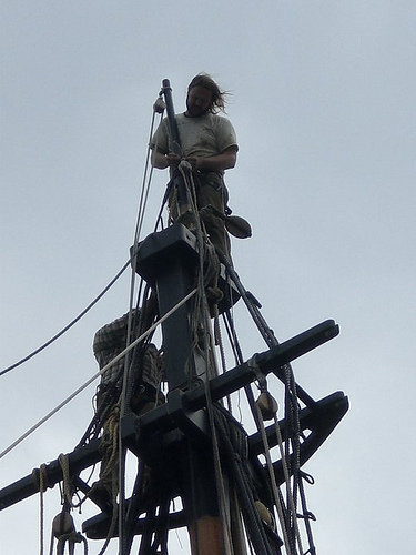Isaiah up at the very tip top of the mast adjusting a part of the royal yard's mechanics.