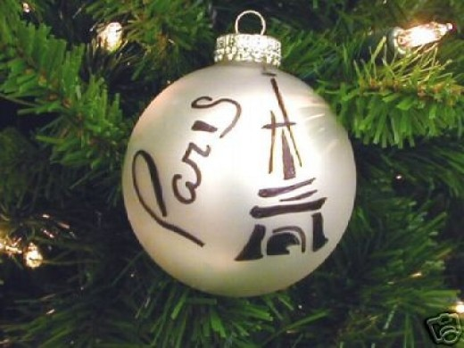 Simple Christmas ornaments can be made by purchasing pearl white plain ball ornaments. Used black paint and puff paint to draw on some of them. This one was an obscure Eiffle Tower shape with Paris written on it.