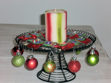 Black wire cake stand with ornaments hung around the edges, candy surrounds a candle in the middle.