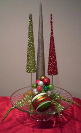 Three tree figurines in back, small bowl with ornaments in front, glitter fronds and large ornament accent.