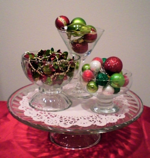 Martini glass and 1 small bowl filled with ornaments, larger bowl filled with garland, placed on a doily on the cake stand.