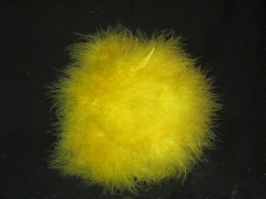 Fluff the feathers around the pins to cover them. Now stick the painted dowel rod into the center of the covered ball.