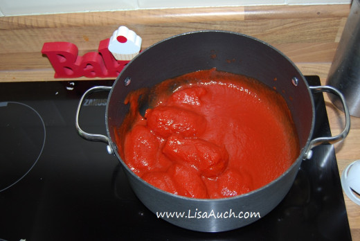 Empty tomatoes into another large pot and blitz smooth with a hand blender