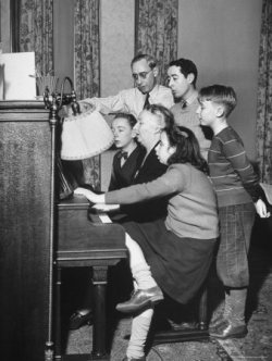 family gathering round a piano