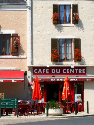 Cafe du Centre with red shutters, parasols and flowers