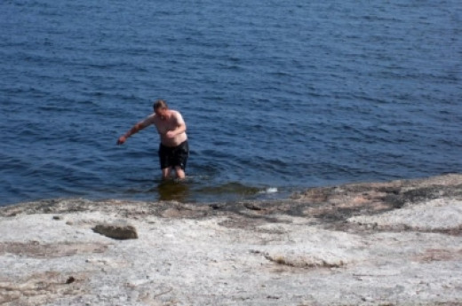 "Steve tries to catch a fish with his bare hands on the shore of ""our"" island."