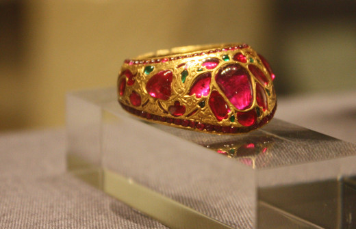 Archer's thumb ring India or Pakistan 17th century Gold, chased and engraved, and set with rubies and emeralds; the inside enamelled in opaque turquoise, pale green, white and black Museum no. IM. 207-1920