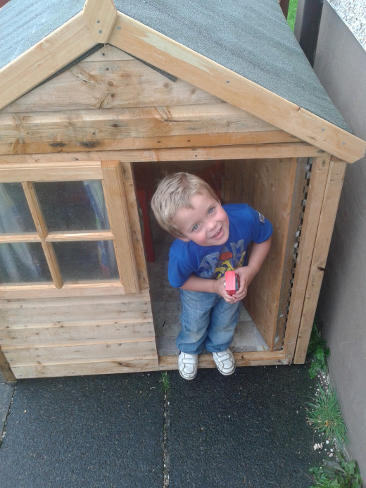 My youngest son demonstrates the mansion we bought from my Hubpages earnings.