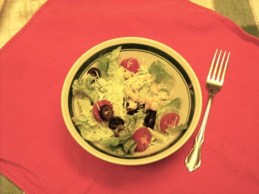 Everyday salad with tomato, garbanzos, olives and Asagio cheese.
