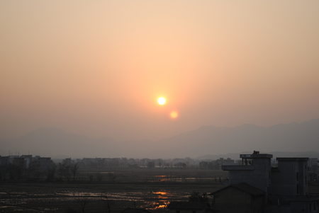 Although many conflicting explanations exist for this image of two Suns captured in China in March of 2014, all the experts have agreed it is not a photoshopped image.