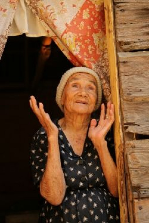 Old Woman with uplifted hands in despair