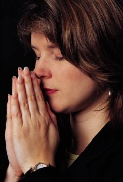 Woman praying with hands clasped