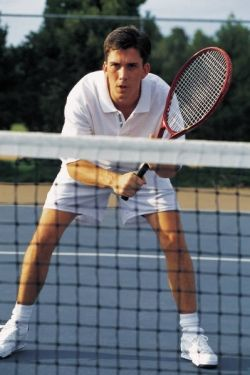 Tennis player at the net with racquet in hand - Volley position
