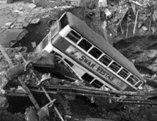 A bus fallen into a bomb crater.