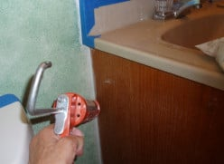 Caulking my bathroom cupboard prior to painting. (Can you see why the room needed painting?)