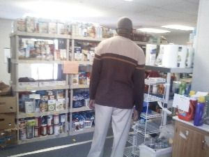 A volunteer looks over the shelves at the food bank (all that food would be gone within just a couple hours)
