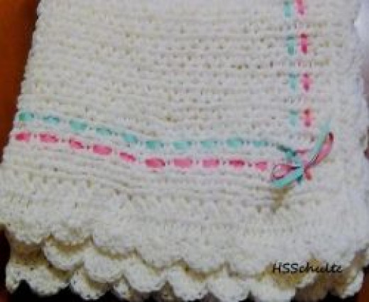 This blanket is 1.75 feet x 1.75 feet. It is loomed with an 8 wrap cast on, the fashion stitch, and the crochet cast off. The shell stitch is crocheted around the edges and a ribbon is woven through the knit.