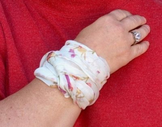 Use a long narrow scarf around the wrist. Tie once and tuck in ends.
