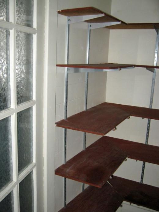 Shelves behind the door and along far wall.