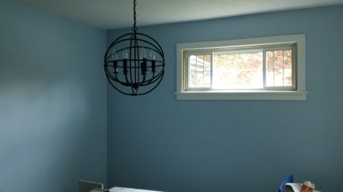 Light fixture in unpainted bedroom.