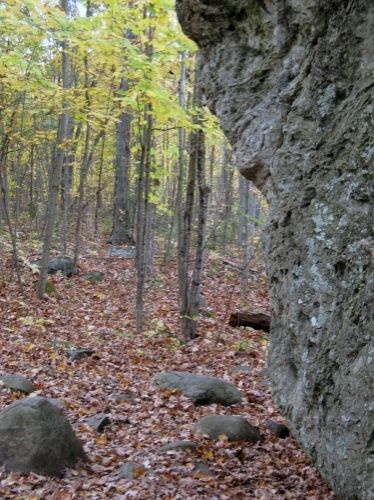 Around the back of the boulder.