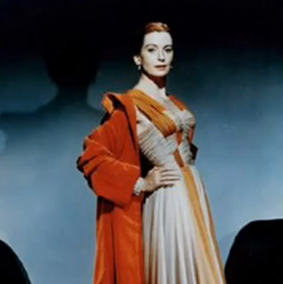 That wonderful dress again, complete with pearls and gorgeous orange coat.