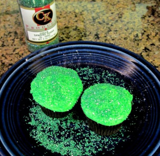Frost the remaining two mini cupcakes with Green Frosting and cover them with green sanding sugar.