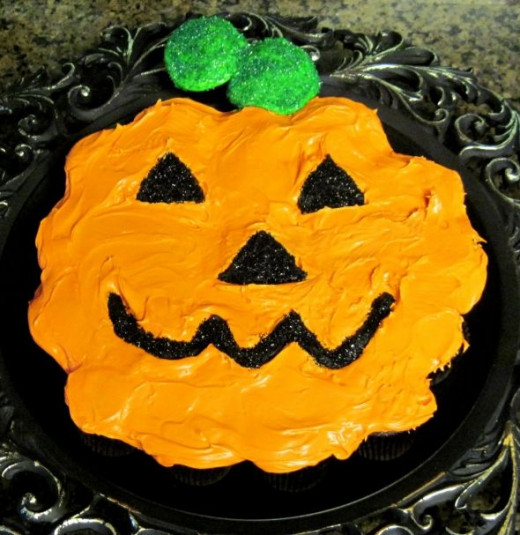 Place the green cupcakes at the top of the pumpkin for the stem.