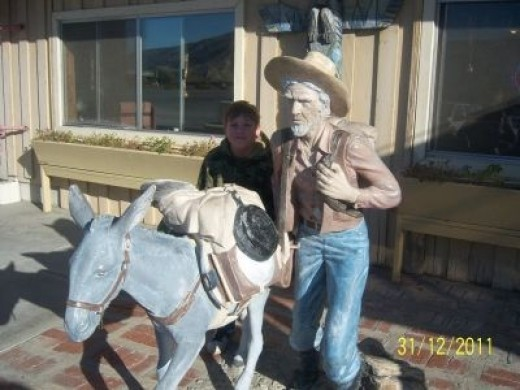 The Claude K. Bell miner and burro at the Wheel Inn