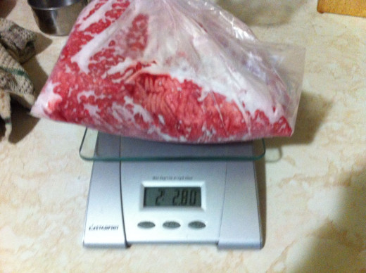 Weighing a pkg of ground beef.
