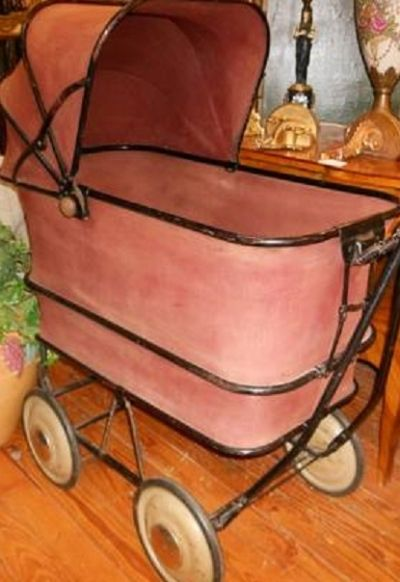 A canvas and leather style carriage with a collaspible hood.