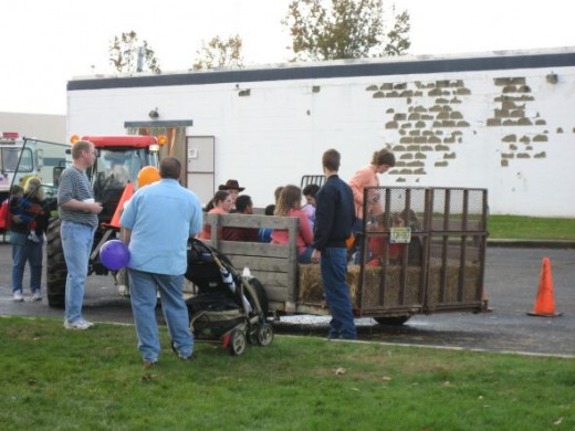 Children in costumes and happy parents get to take a scenic hay ride around the area