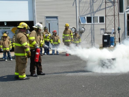 Firefighters demonstrate and then let teenagers learn hands on how to use fire extinguishers.