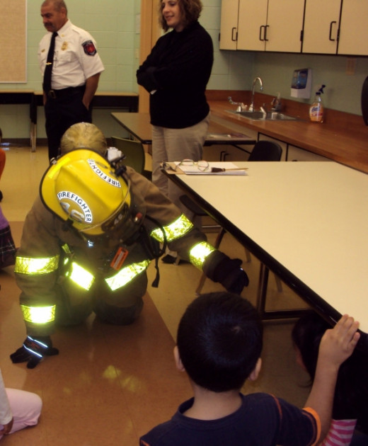 Sometimes firefighters even have to coax children into trusting them as this firefighter had to do one year at a local school. Once he geared up, the child scooted under the nearest table. By the time we left she had a big kiss for all the firefighte