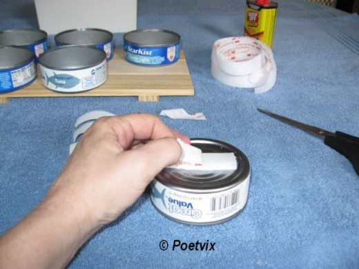 Using the same Velcro for all cans, peel the backing and stick it to the back of the can. Put the opposite type over it so they join.