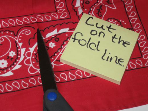 Step three - cut bandanna laterally along the fold line.