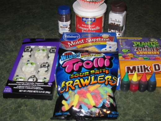 What you need - A box cake mix, white frosting, food coloring, a paintbrush for food, gummy mummies, chocolate sprinkles, toothpicks and gummy worms