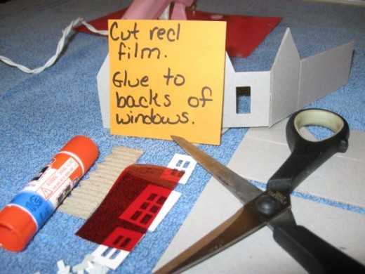 Cut the red film and glue or tape to the interior walls behind the windows and door.