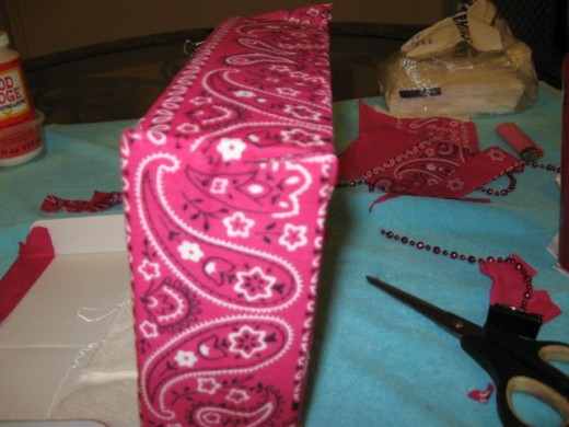 Make a slit and trim the bandanna to keep the hole in the back accessible.