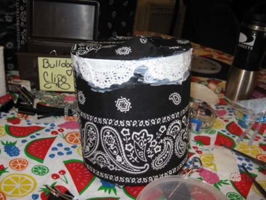 I found turning the can over and making a platform of the bulldog clips made it easier to work. Use liberal coats of Mod Podge on the front and back of the doilies.