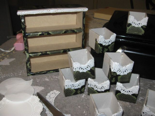 To do the drawers, simply cover in tape. Above the tape line, I cut off the lacy parts of the doily and taped it down covering the top parts of the drawer fronts. When all were assembled, Mod Podge was applied.