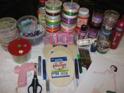 Needed: Unfinished wood plaques, paper dolls, scissors, glue, Mod Podge, fake string of pearls, glitter nail polish, glitter, glue gun, ribbon.